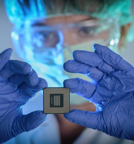 Technician in clean room garb holding a semiconductor device