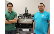 Amritesh Rai and Maruthi Yogeesh standing on either side of scientific instrument