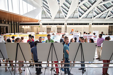 Students in EER building atrium, sharing research posters