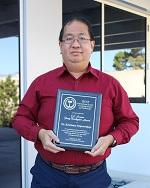 Dr. Kristianto Tjiptowidjojo, Research Assistant Professor, Department of  Chemical and Biological Engineering, University of New Mexico holding the awarded plaque