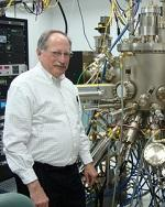 Dr Brueck next to a complex vacuum chamber